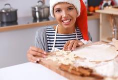 Femme faisant des biscuits de Noël dans la cuisine Photographie stock libre de droits