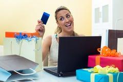 Femme faisant des emplettes en ligne avec l'ordinateur portable regardant votre carte de crédit Images stock