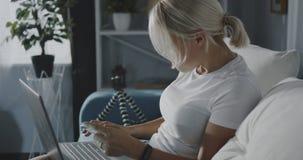 Femme faisant des emplettes en ligne avec l'ordinateur portatif banque de vidéos