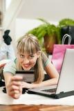 Femme faisant des emplettes en ligne par l'intermédiaire de l'Internet de la maison Photo stock