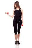 Femme faisant des exercices avec des haltères rouges Photographie stock libre de droits