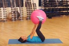 Femme faisant des exercices avec la boule convenable de rose dans la classe de gymnase de forme physique Les femmes d'aides de bo photographie stock