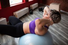Femme faisant des exercices avec le fitball dans la classe de gymnase de forme physique Muscles abdominaux s'engageants de noyau  photos libres de droits