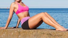 Femme faisant des exercices de sports dehors par le bord de la mer Image stock