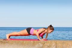 Femme faisant des exercices de sports dehors par le bord de la mer Photographie stock libre de droits