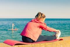 Femme faisant des exercices de sports dehors par le bord de la mer Photos stock