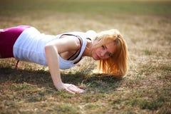 Femme faisant des exercices pour des muscles, s'exerçant dehors images libres de droits
