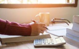 Femme faisant des finances et calculant sur le bureau de table ? la maison Finances et ?conomie de concept avec le livre dans le  images libres de droits