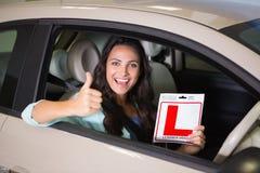 Femme faisant des gestes des pouces tenant un signe de conducteur d'étudiant Image stock