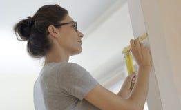 Femme faisant des murs d'une rénovation à la maison et de mesure avec une règle image stock
