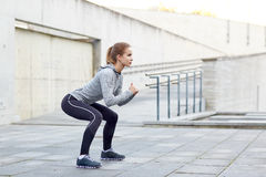 Femme faisant des postures accroupies et s'exerçant dehors Photo stock