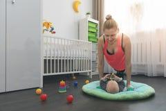 Femme faisant des pousées à la maison tout en jouant avec son petit bébé image libre de droits