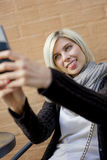 Femme faisant des visages tout en prenant Selfie au café extérieur Photo libre de droits