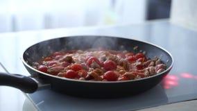 Femme faisant frire les légumes et le boeuf avec des tomates banque de vidéos