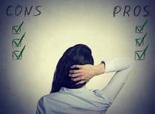 Femme faisant l'évaluation de recherches de risque se tenant au mur avec le pour - et - le contre Images stock