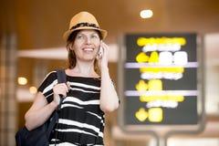 Femme faisant l'appel devant le conseil de l'information dans l'aéroport Images stock
