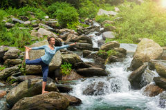 Femme faisant l'asana Natarajasana de yoga dehors à la cascade Images stock
