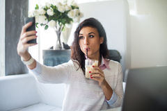 Femme faisant l'autoportrait avec un appareil-photo de téléphone portable dans le restaurant prenant la photo au téléphone intell Image libre de droits