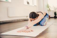 Femme faisant l'exercice et la forme physique de yoga à la classe de studio images stock