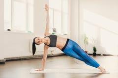 Femme faisant l'exercice et la forme physique de yoga à la classe de studio photographie stock
