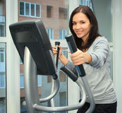 Femme faisant l'exercice sur un entraîneur elliptique Images libres de droits
