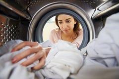 Femme faisant la blanchisserie atteignant la machine à laver intérieure photo libre de droits