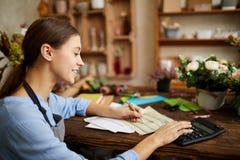 Femme faisant la comptabilité dans le magasin image stock