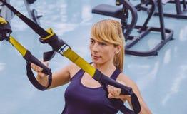 Femme faisant la formation de suspension avec la forme physique photographie stock
