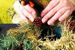Femme faisant la guirlande de Noël Images stock