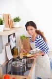 Femme faisant la nourriture saine se tenant souriante dans la cuisine Images libres de droits