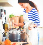 Femme faisant la nourriture saine se tenant souriante dans la cuisine Image stock