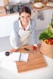 Femme faisant la nourriture saine se tenant souriante dans la cuisine Photographie stock libre de droits