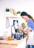 Femme faisant la nourriture saine se tenant souriante dans la cuisine Photographie stock