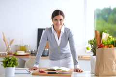 Femme faisant la nourriture saine se tenant souriante dedans Image stock