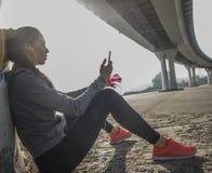 Femme faisant la pause de la séance d'entraînement et écoutant la musique Image libre de droits