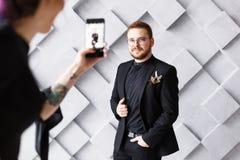 Femme faisant la photo du marié au téléphone à l'arrière-plan gris de studio d'isolement Image libre de droits