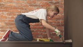 Femme faisant la pièce de réparations peignant l'étagère banque de vidéos