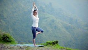 Femme faisant la pose d'arbre d'asana de yoga dehors banque de vidéos