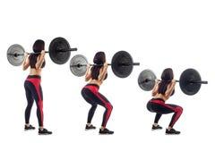Femme faisant la posture accroupie avec un barbell photo libre de droits