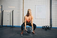 Femme faisant la séance d'entraînement de crossfit avec le medicine-ball au gymnase Photographie stock