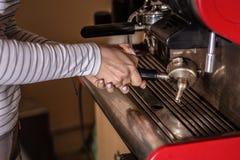 Femme faisant le café d'expresso sur une machine professionnelle dans la barre photos stock