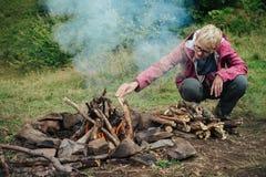 Femme faisant le feu dans le camp de montagne photos libres de droits
