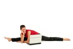 Femme faisant le fractionnement avec l'ordinateur portatif Photographie stock libre de droits
