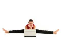 Femme faisant le fractionnement avec l'ordinateur portatif Photographie stock
