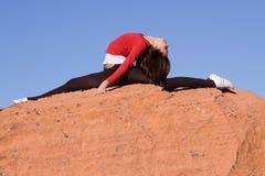 Femme faisant le fractionnement sur les roches Photographie stock