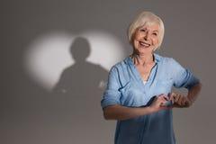 Femme faisant le geste et la position d'amour dans le studio avec l'ombre en forme de coeur Images libres de droits