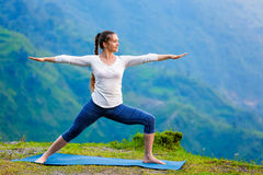 Femme faisant le guerrier de Virabhadrasana 2 d'asana de yoga d'Ashtanga Vinyasa images stock
