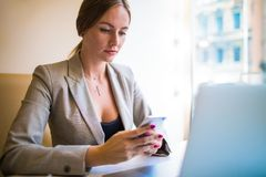 Femme faisant le magasin de achat en ligne par l'intermédiaire du téléphone portable après vidéoconférence sur l'ordinateur porta images stock