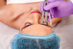 Femme faisant le maquillage permanent photos stock