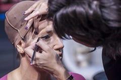 Femme faisant le maquillage sur le visage avec des cosmétiques Images stock